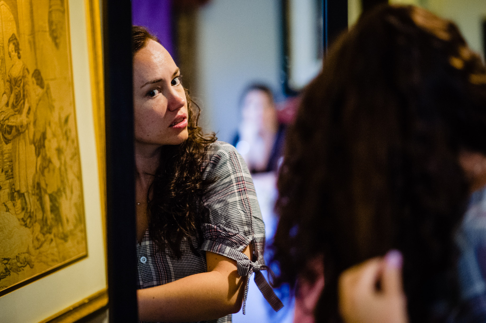The bride styles her own hair in the mirror