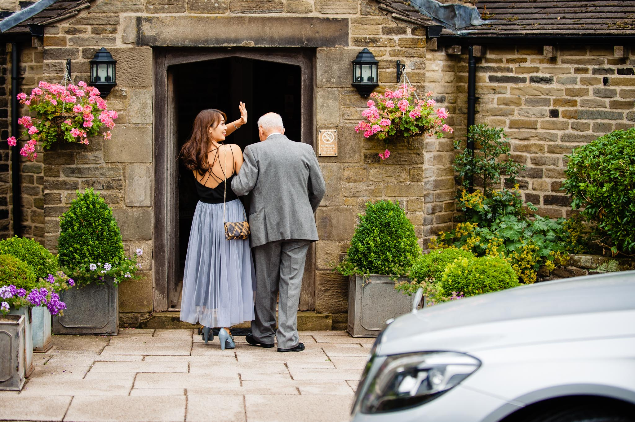 A guest waves to an old friend as she leads an elderly gentleman into Holdsworth House