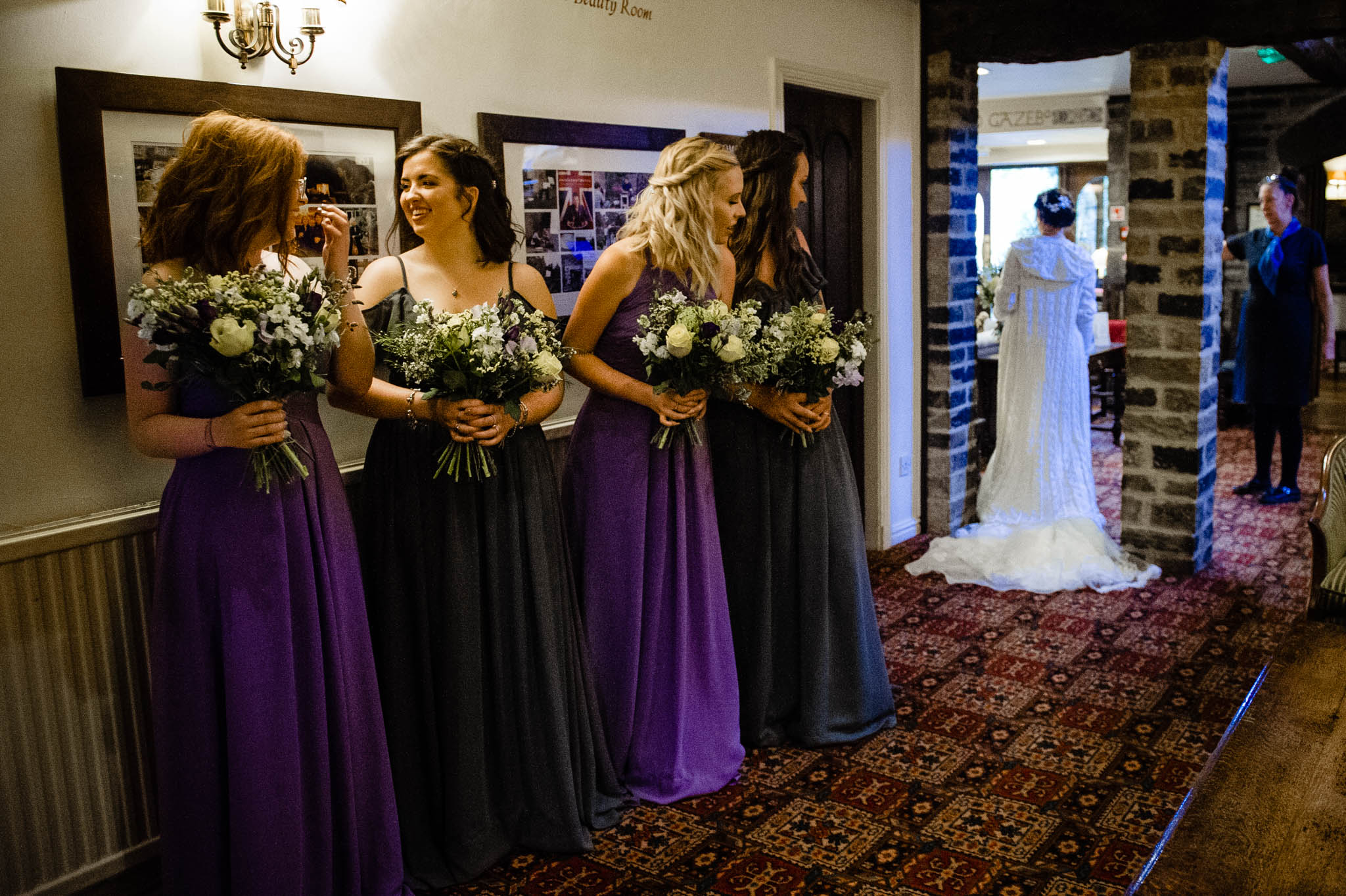 The bridesmaids see the bride in her dress for the first time
