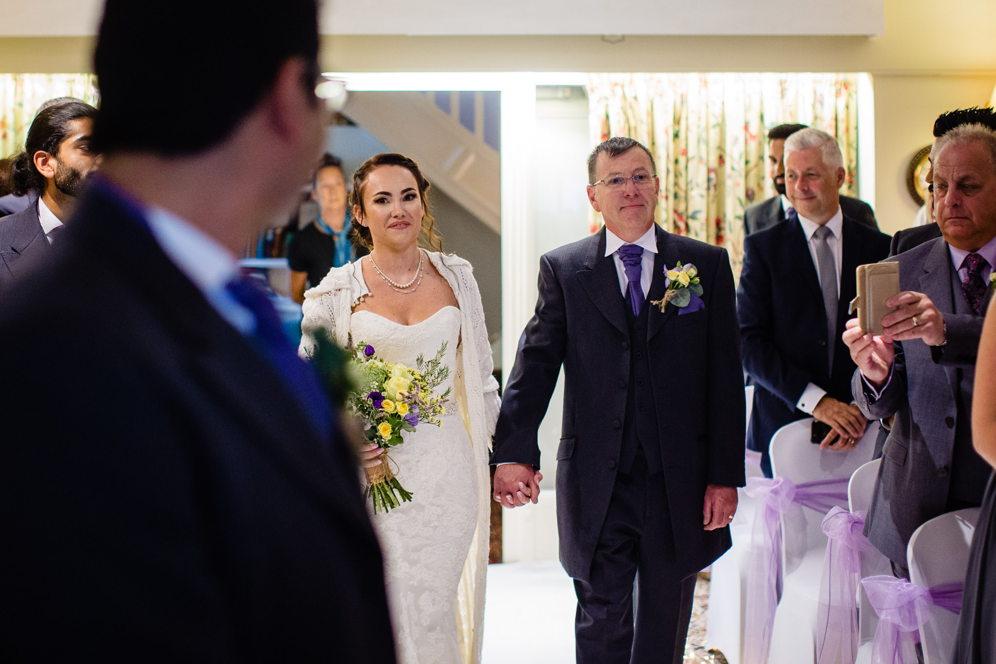 Father of the bride leads his daughter up the aisle