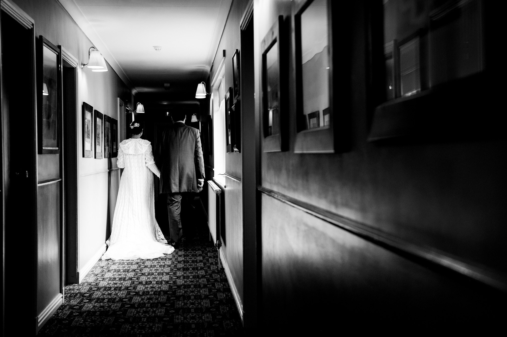 Bride and groom walk down a corridor with moody lighting