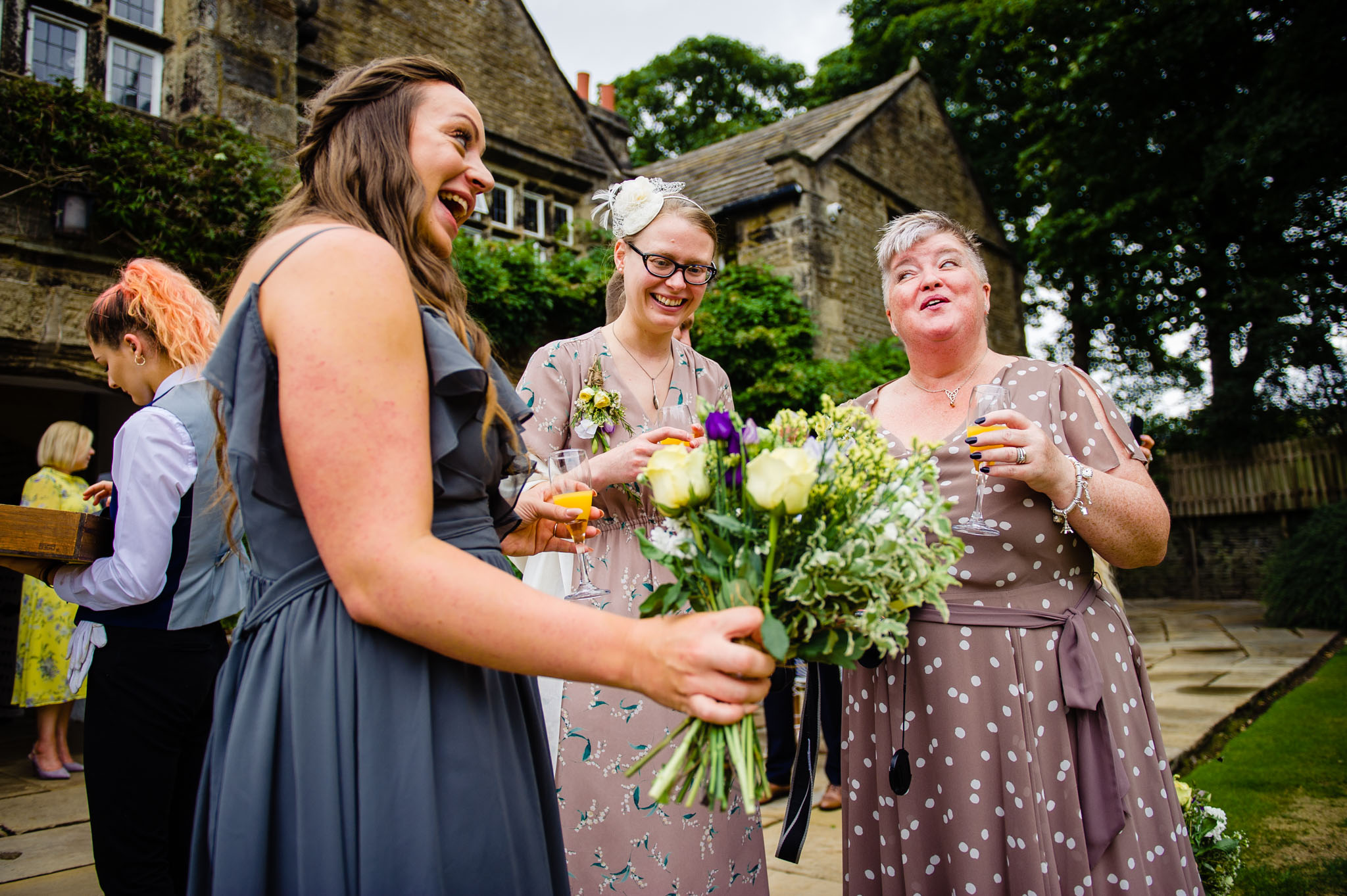 Bridesmaids and guests have a laugh over some bubbly