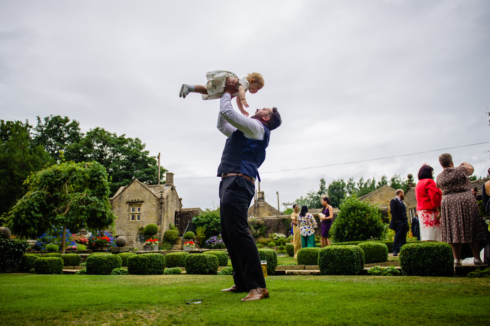Wedding guest swings their child round in the air