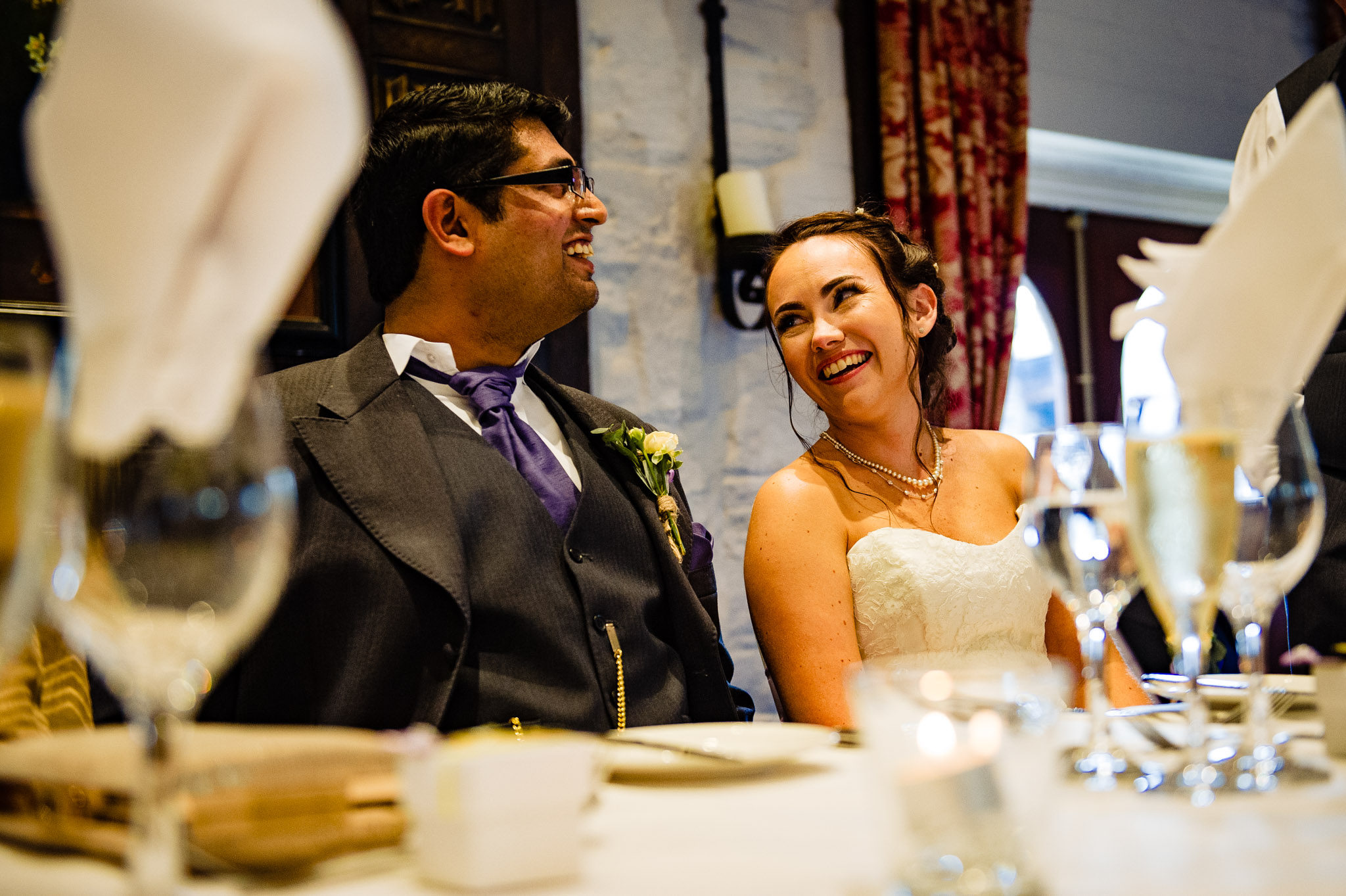 Bride and groom share a moment during the speeches - Holdsworth House Wedding Photography
