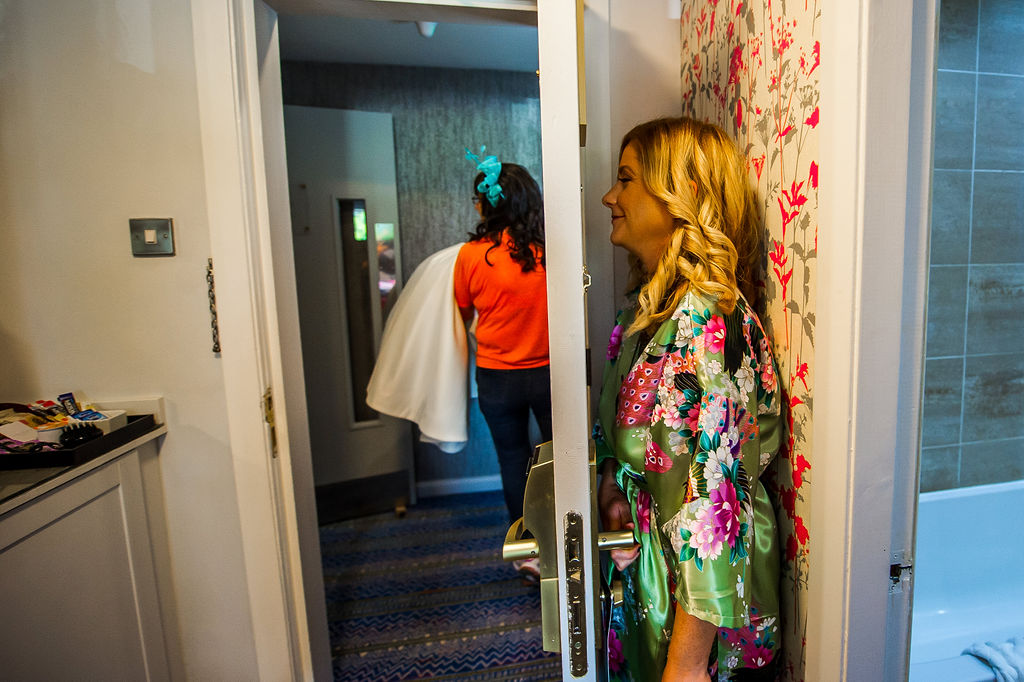 mum carries the dress while a bridesmaid is trapped behind a door