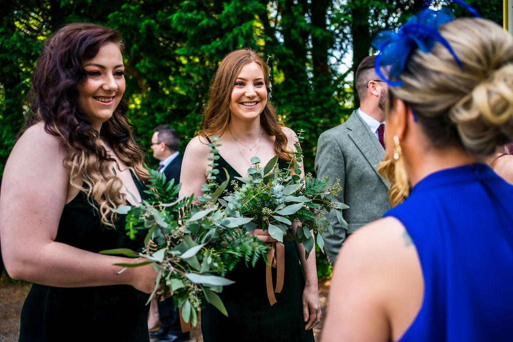 Bridesmaids smile with other wedding guests