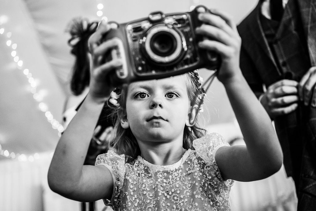 Flower girl takes a photo on her camera