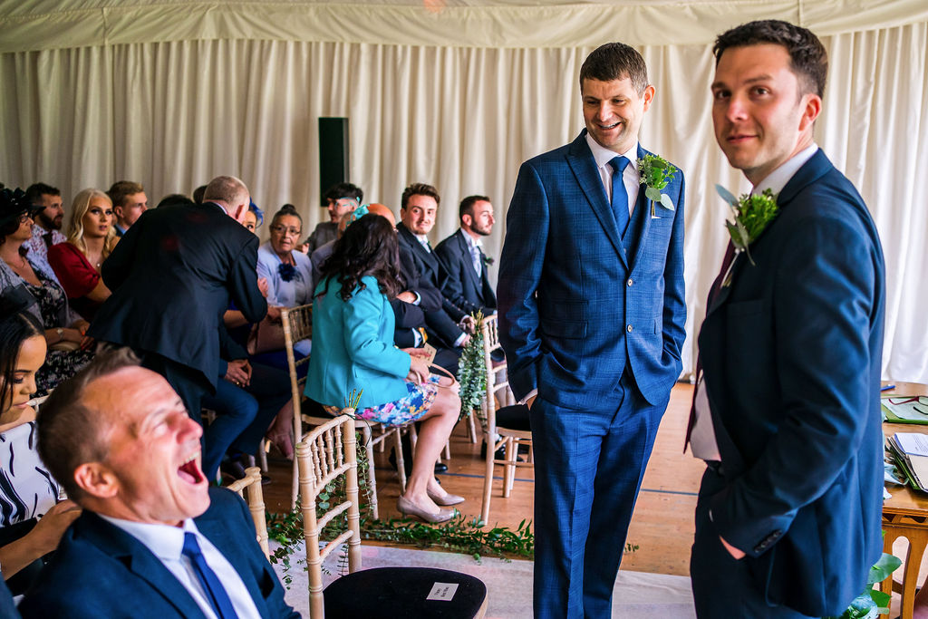The groom shares a joke with a wedding guest before the ceremony