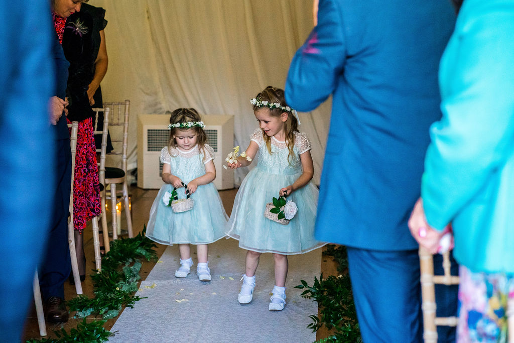 The folower girls lead the bride down the aisle