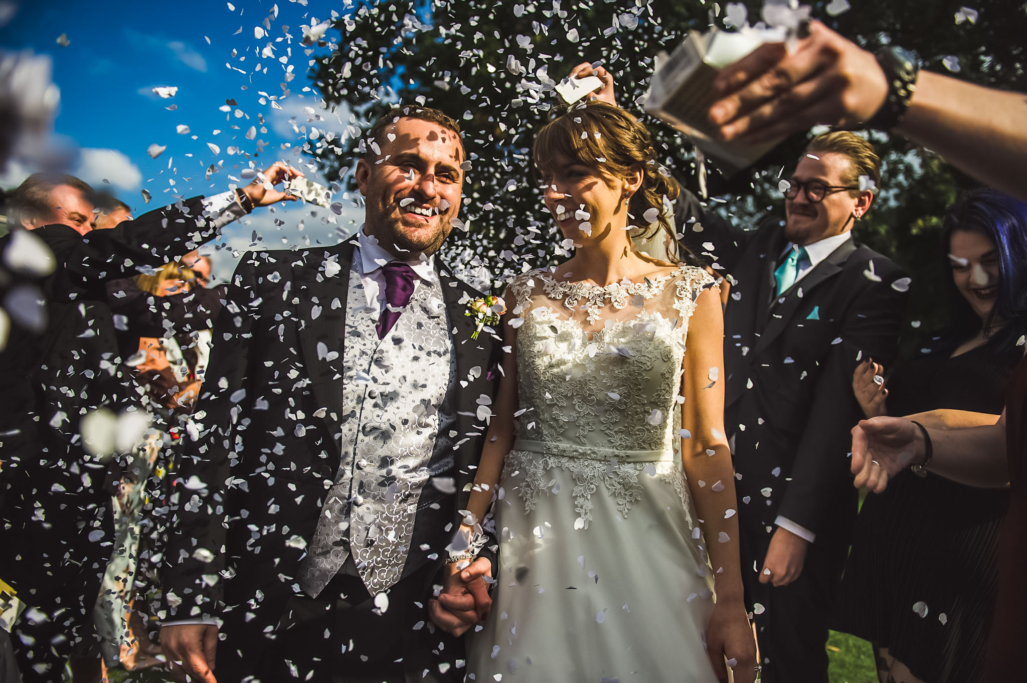 Bride and Groom are covered in confetti - wedding photography in Manchester